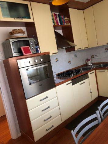 Cucina con elettrodomestici, tavolo e sedie