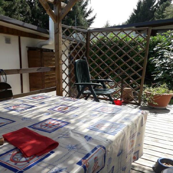 Casetta in legno con giardinetto e grande veranda.